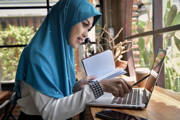 彼女のホームオフィス、ビジネスアイデアでタブレットを介してチャットでビジネスを議論するイスラム教徒の女性