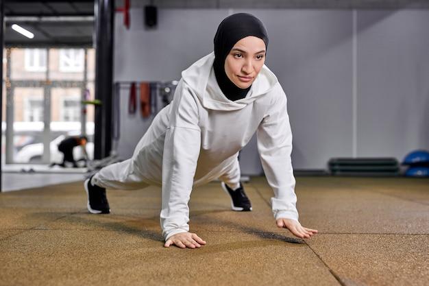 イスラム教徒の女性は腕立て伏せをします。現代のジムのフィットネスセンターで一人で実行している強くてフィットする運動アラビアの女性。トレーニングトレーニング、スポーツコンセプト