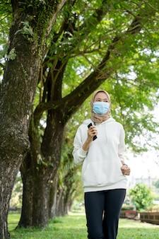 Мусульманка занимается спортом и использует маску на открытом воздухе, чтобы предотвратить распространение вируса