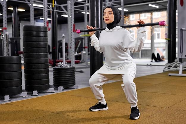 現代のフィットネスジムでのスポーツトレーニングトレーニング中にバーベルから空のハゲタカを持ち上げるスクワットをしているイスラム教徒の女性。健康的なライフスタイルとスポーツの概念