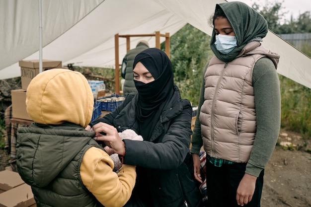 난민 텐트에서 이슬람 여자 드레싱 딸
