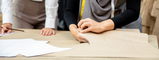 Muslim woman dressmaker cutting clothing pattern at the table in tailor shop