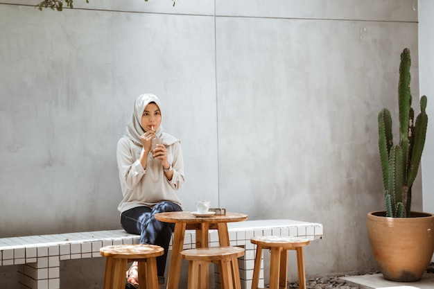 Muslim woman enjoying drinking ice coffee