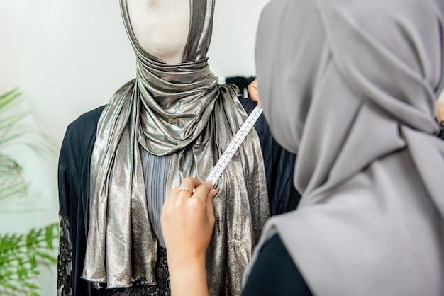 Muslim woman fashion designer measuring size of the dress