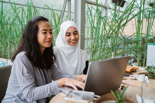 Muslim woman and friend discussing with laptop