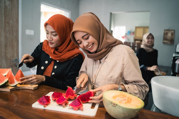 Muslim woman friend preparing some fruit dessert cocktail