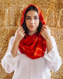 Muslim woman in front of golden wall