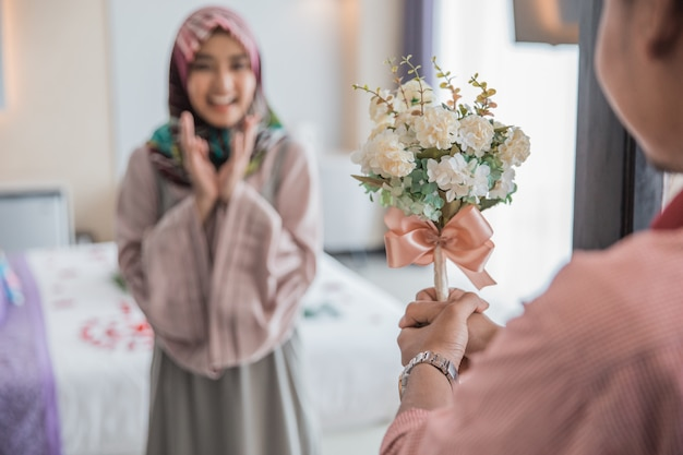 Muslim woman having a flower from man