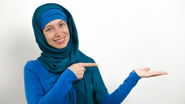 A muslim woman in a hijab is pointing fingers at a copy space.