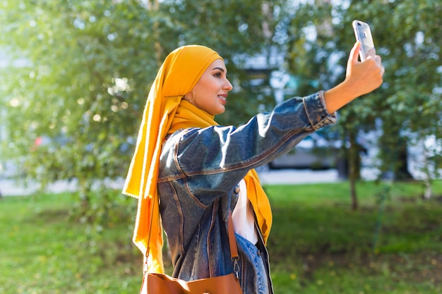 Muslim woman in hijab makes a selfie on the phone standing on the street of the city
