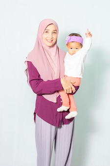 Muslim woman holding her little daughter on her left arm.