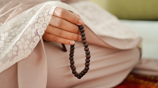 Muslim woman holding prayer beads for dhikr after performing salat