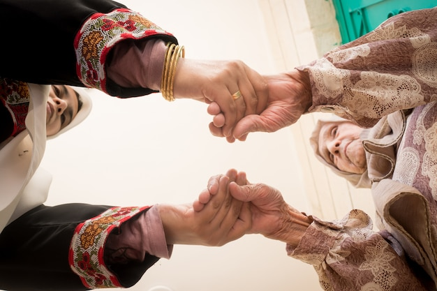 Muslim woman holding senior grandmother hands