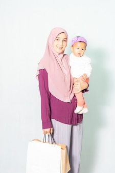 Muslim woman holding shopping bag and her little daughter.