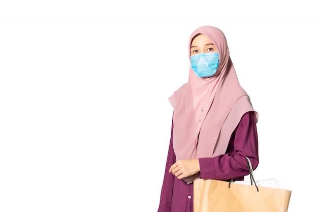 ホワイトスペースに分離された買い物袋を保持しているイスラム教徒の女性。