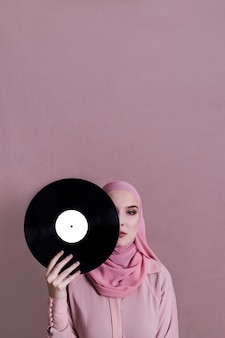 Muslim woman holding vinyl in front of face