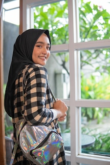 Muslim woman at home by the window