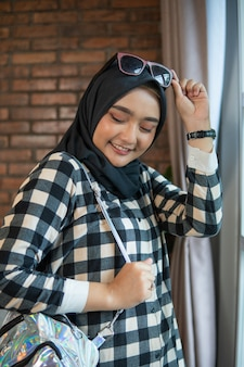 Muslim woman at home with sunglasses