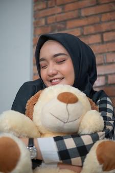 Muslim woman hugging her stuffed animal