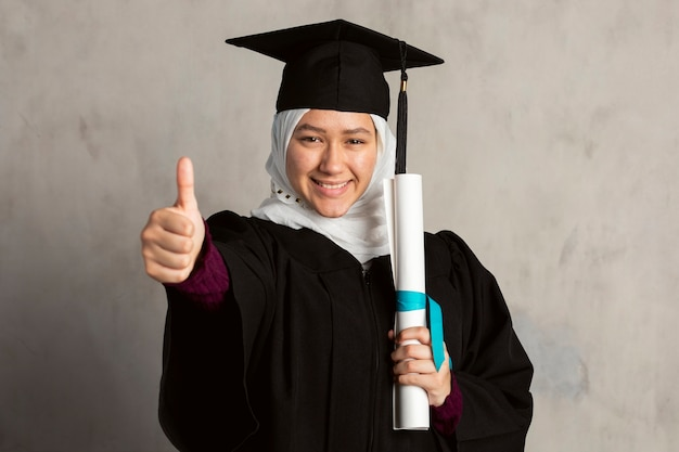 彼女の卒業証書を保持している卒業式のガウンのイスラム教徒の女性