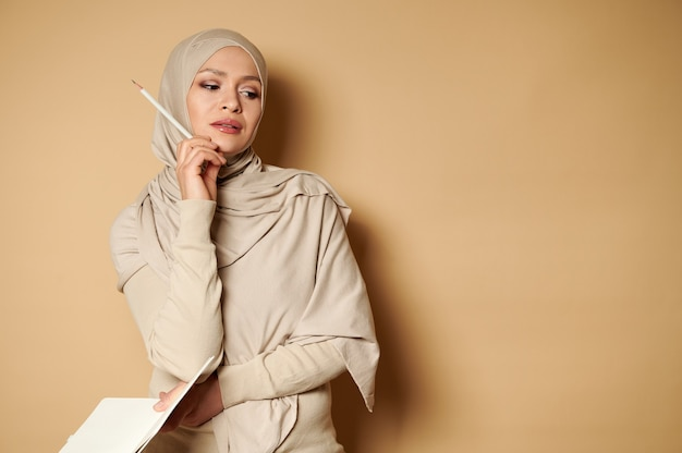 物思いにふける表情のヒジャーブを着たイスラム教徒の女性が、片手に日記を、もう片方の手にあごに鉛筆を持ってベージュの表面に立っています。