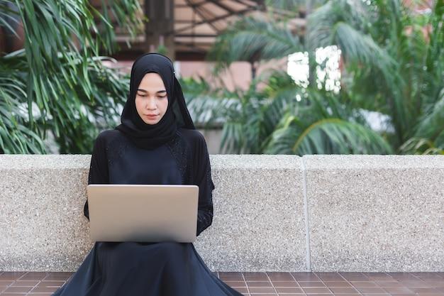 ノートパソコンの屋外オフィスで働く黒のヒジャーブのイスラム教徒の女性。