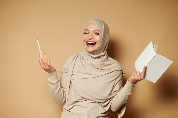 メモ帳と鉛筆を持って、コピースペースのあるベージュの表面で正面にポーズをとって笑っているヒジャーブのイスラム教徒の女性