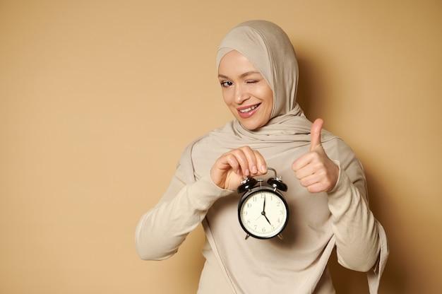 ヒジャーブのイスラム教徒の女性は手に目覚まし時計を持って、コピースペースのあるベージュの表面で正面を見て親指を示しています