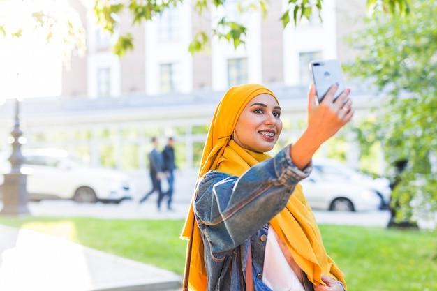 ヒジャーブのイスラム教徒の女性が街の通りに立っている電話で自分撮りをします