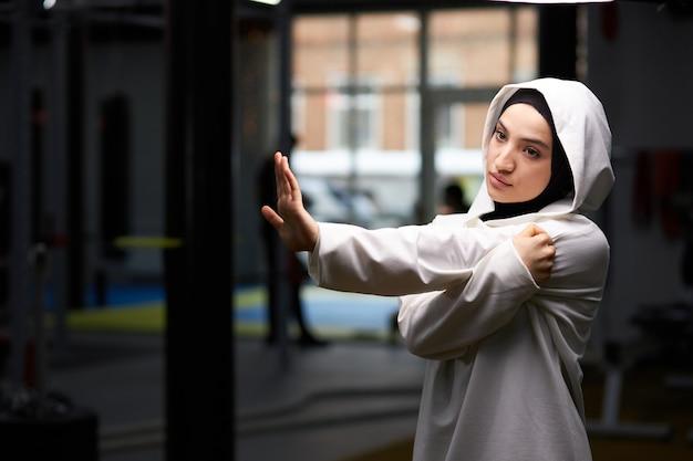 トレーニングの準備をしているジムで体を伸ばしているヒジャーブのイスラム教徒の女性は、一人で、運動をします。体操。スポーツ、フィットネス、健康的なライフスタイルのコンセプト
