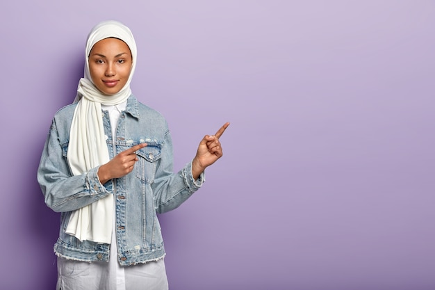 무슬림 여성이 커피를 마시고 오른쪽을 가리키며 흰색 베일과 데님 재킷을 입습니다.