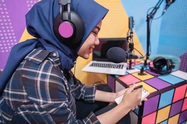 이슬람 여성이 펜으로 메모하는 노트북으로 스튜디오에서 팟캐스트를 녹음하고 있습니다