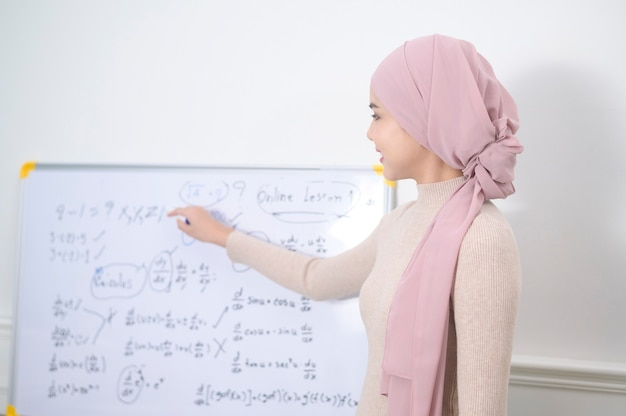A muslim woman lecturer using laptop for lecturing online via internet. e-learning and telecommunication concept