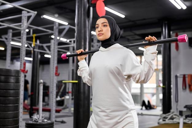 Мусульманская женщина снимая пустую штангу во время спортивной тренировки в современном фитнес-зале. концепция здорового образа жизни и спорта