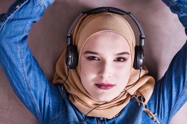 Muslim woman listening to music on headphones