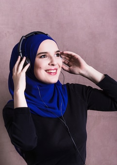 Muslim woman listening to music on headphones