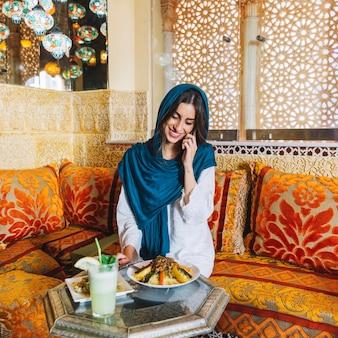 Donna musulmana che fa telefonata nel ristorante