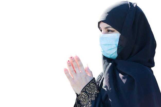 A muslim woman in a medical mask prays to god. isolated.