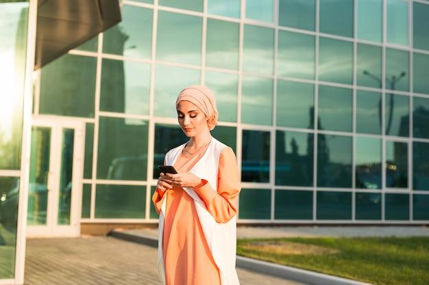 Мусульманка обменивается сообщениями по мобильному телефону в городе