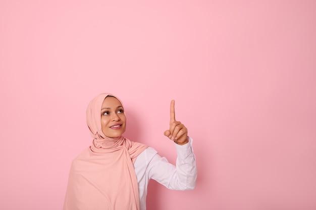 宗教的な衣装に身を包み、ヒジャーブ民族で頭を覆った中東民族のイスラム教徒の女性は、歯を見せる笑顔で微笑んで、ピンクの背景のコピースペースに人差し指を向けて見上げる