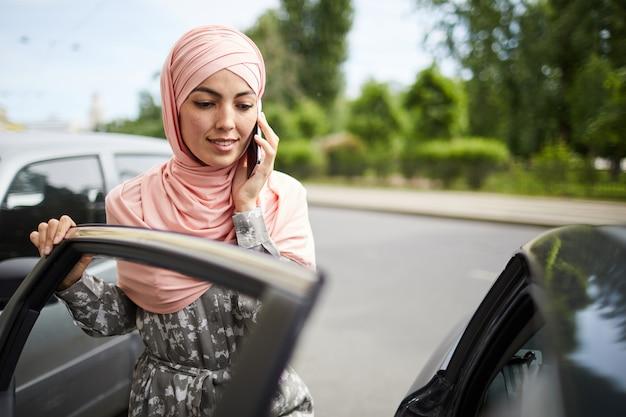 イスラム教徒の女性が車のドアを開く