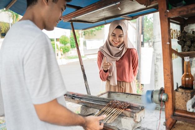 小さなフードカートの売り手にチキンサテを注文するイスラム教徒の女性