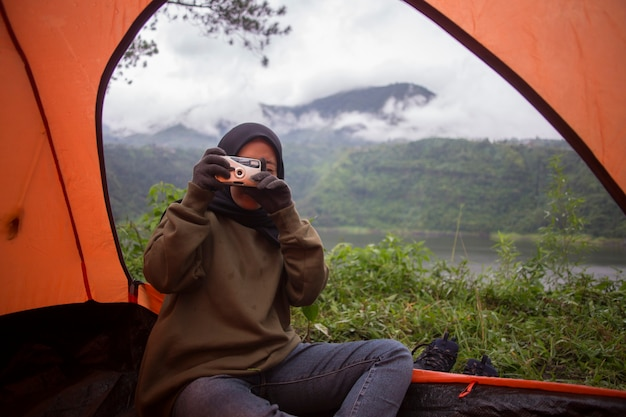 A muslim woman photographing in tent