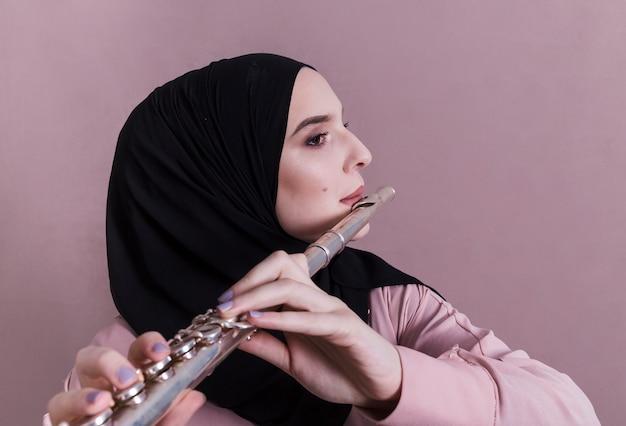 Donna musulmana che suona il flauto