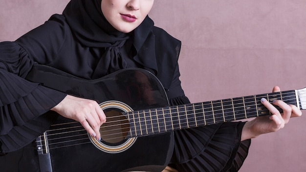 Muslim woman playing on the guitar