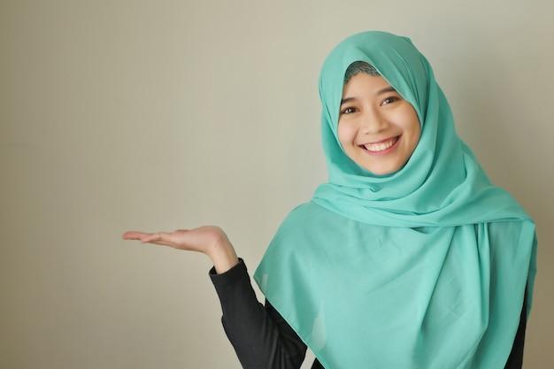 空白スペースに手を指しているイスラム教徒の女性