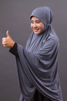 Muslim woman pointing thumb up side way, asian islamic woman model