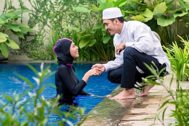 Muslim woman in pool greeting her husband