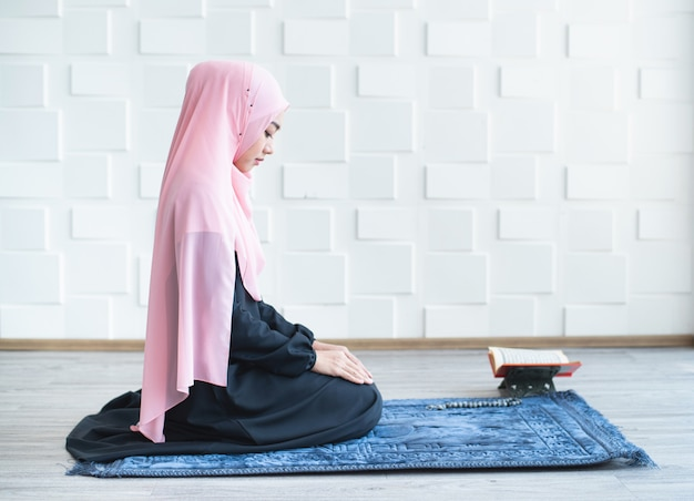 Muslim woman pray on hijab praying on mat indoors