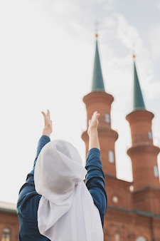 Muslim woman prayer wear hijab fasting pray to allah on mosque back view